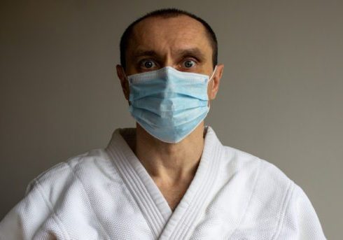 A young strong man in a white kimono for sambo, jiu jitsu and other martial arts with a blue medical gloves and medical mask. Fright emotion.